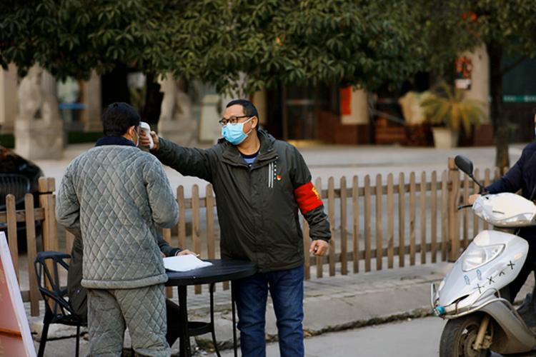 2月19日,文化館的金勁松,給出入小區的居民測量體溫。