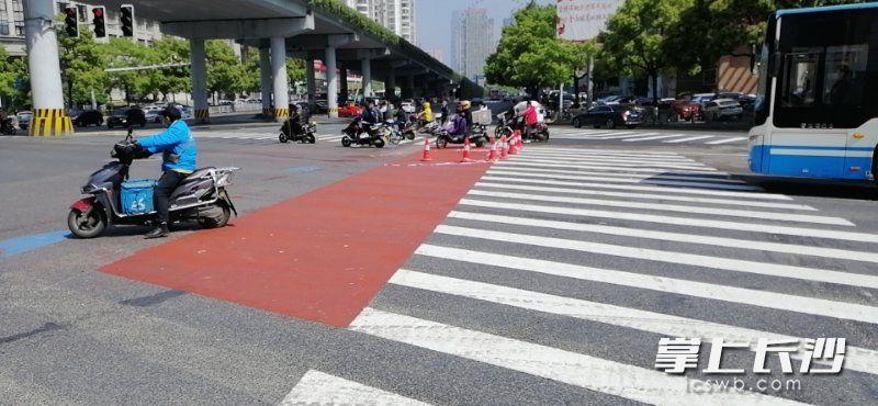 """在芙蓉路劳动路口,路面上的红色区域为非机动车""""蓄水池等候区""""。 天心交警供图"""