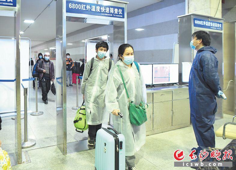 ↓4月8日凌晨,K81次列车到达长沙火车站,两名从武汉来的乘客通过测温设备出站。  新华社记者 薛宇舸 摄