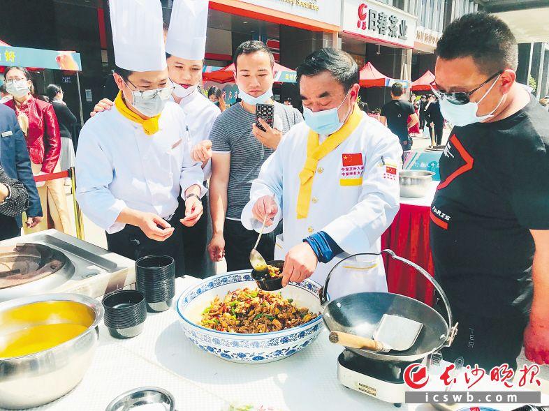许菊云大师(右二)献技做茶油炒土鸡。 长沙晚报全媒体记者 李卓 摄