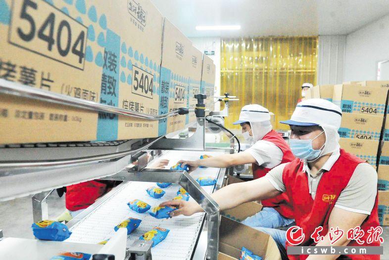 张韦韦正在薯片外包车间流水线上作业。长沙晚报全媒体记者 贺文兵 摄