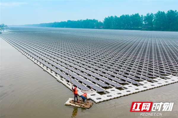 图2:4月22日,中国能建浙江火电的工作人员划着浮排登上光伏设备进行检查。.jpg