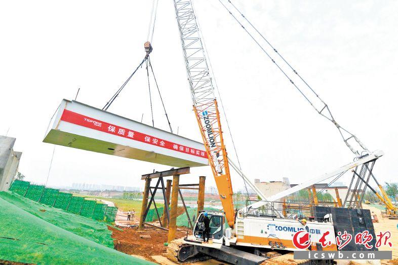 24日,在长沙高铁新城,连接浏阳河东西两岸的步行廊桥首段钢箱梁顺利吊装完成。 长沙晚报全媒体记者 王志伟 摄