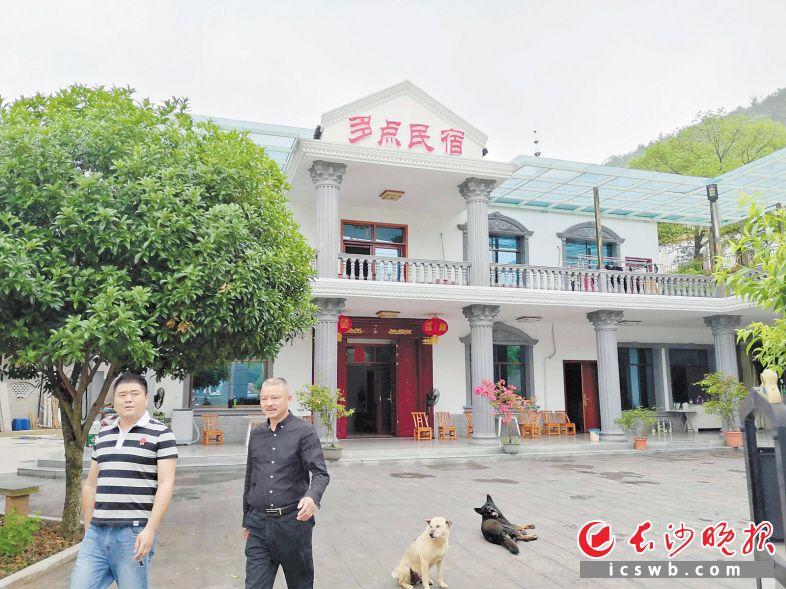 """利用自己房子改造成""""多点""""民宿的村民张永波(右)对未来充满了信心。长沙晚报全媒体记者 贺文兵 摄"""