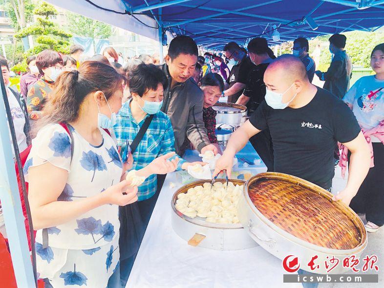"""""""湖南好人""""吴鑫成(右)带了20余笼包点,免费送给市民品尝。   长沙晚报全媒体记者 李卓 摄"""