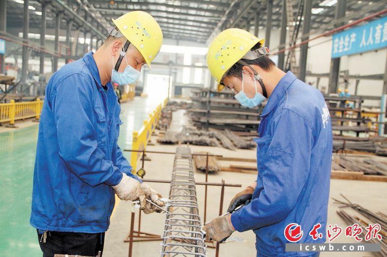 中建科技湖南有限公司的PC工厂里,工人们正在绑扎钢筋笼子。陈燕 摄