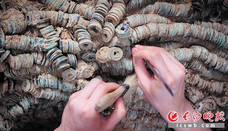 文物修复师小心翼翼地对一堆古钱币进行初次清理。均为长沙晚报全媒体记者 邹麟 摄