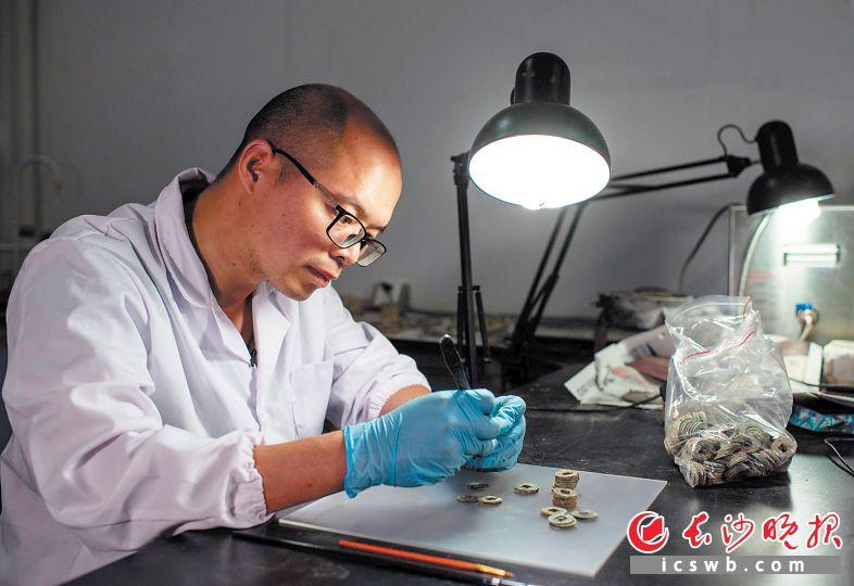 文物修复师莫泽在灯光下对古钱币表面的污渍进行清理。