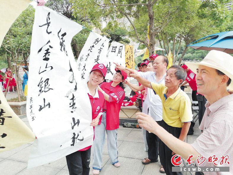 在宁乡市沿江风光带广场,银发志愿者为市民送上现场书写的书法作品。  长沙晚报全媒体记者 张禹 通讯员 刘石江 摄影报道
