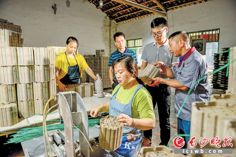 孙见鹏(右一)在连引车间向扶贫队员戴洪举(右二)介绍花炮生产情况。  长沙晚报全媒体记者 陈飞 摄