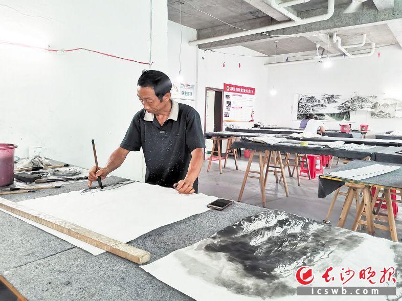 """在新河村韵墨缘画室,""""农民画师""""詹秋明正在画画。长沙晚报全媒体记者 黄能 摄"""