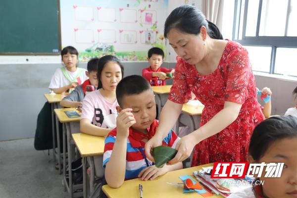 老师为学生演示包粽子的方法。.jpg