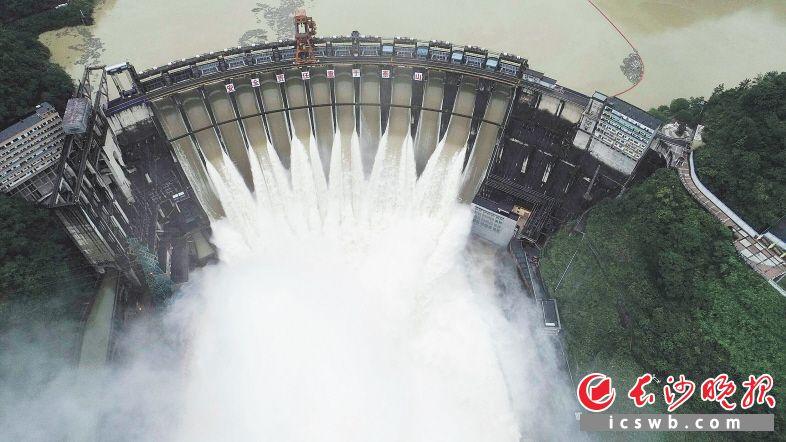 强降雨导致水位上涨,6月22日,沅陵县凤滩水库开启全部闸门泄洪。   新华社发(瞿宏红 摄)
