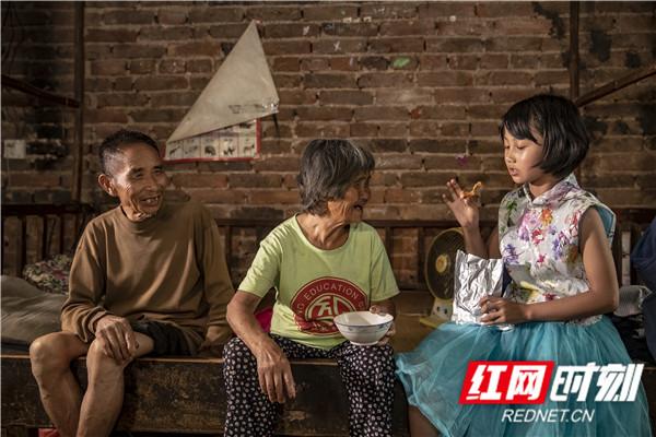 20,端午节,爷爷奶奶拿出亲戚送的酱板鸭给孙女吃,看着小雅吃的很开心,这两名老人也露出幸福的笑容。.jpg