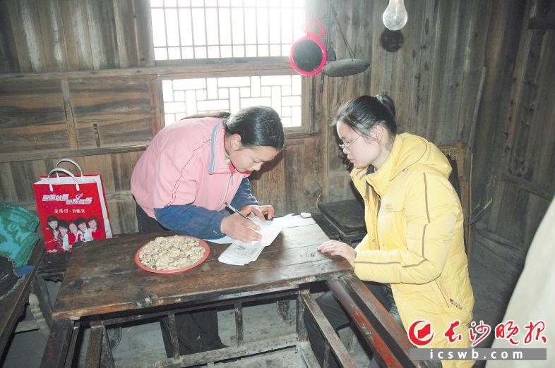 李敏(右)16年来致力于贫困学生的帮扶资助工作,图为她生前走访贫困学生。资料图片