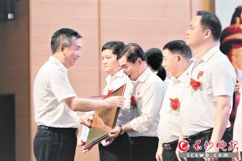 宁乡市联镇领导(左)为先进基层党组织授牌。