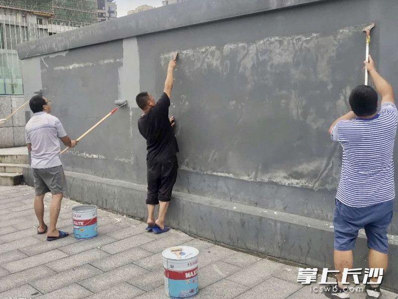 """清除破损广告、重新粉刷墙面,为韶山路沿线""""洗脸打粉""""。"""