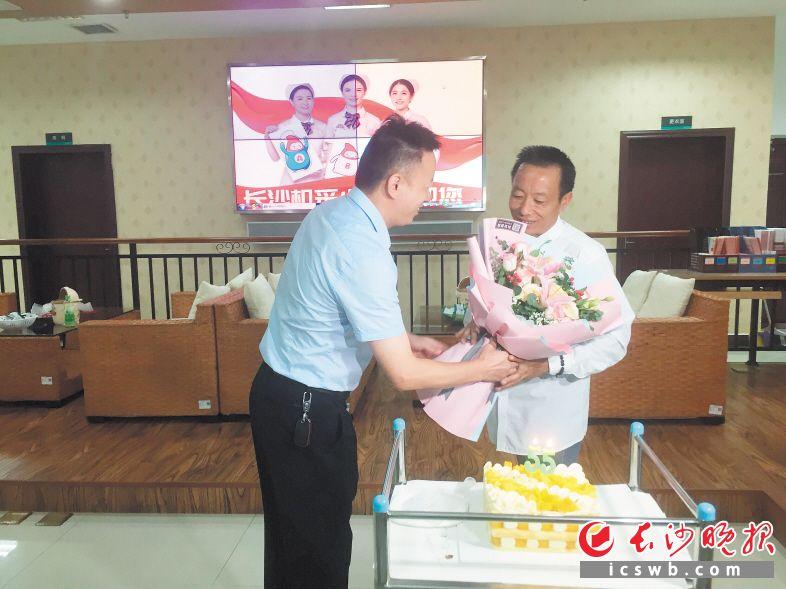 长沙血液中心有关负责人为费必武送上鲜花,祝他生日快乐。  长沙晚报全媒体记者 朱炎皇 实习生 邹菁 摄影报道
