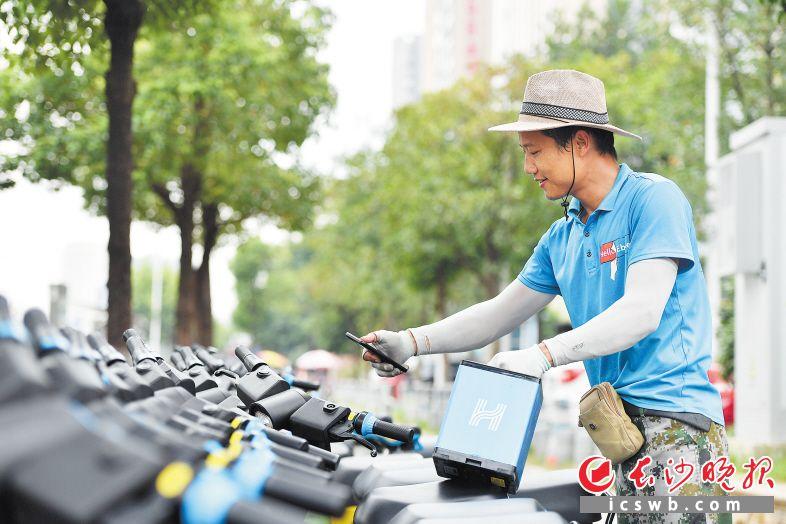 7月30日下午,长沙大道地铁站2号出口附近,胡尚立给共享电单车换上满电电池。长沙晚报全媒体记者 王志伟 摄