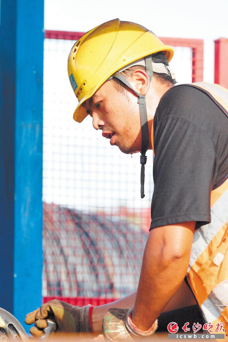施工现场,一名钢筋工在紧张劳作,太阳炙烤下,大颗的汗珠从他的脸颊滑落。 均为长沙晚报全媒体记者 王志伟 摄