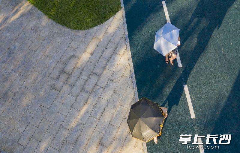 两位游客漫步在小道上,边走边拍照。