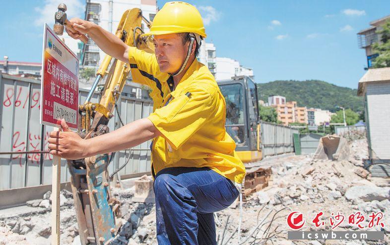 8月3日,阜埠河地铁站沿线,新奥燃气巡线员刘川南给施工路段竖上牌子,提醒施工人员注意安全。
