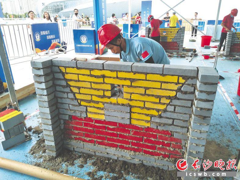 图为比赛现场,选手们在砖砌作品。