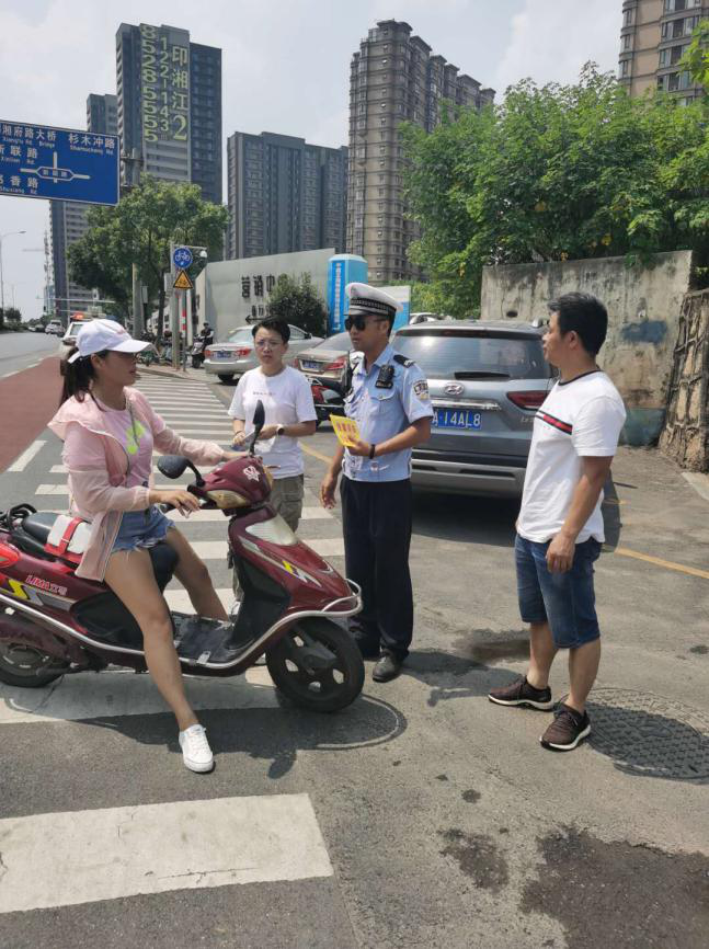 街道公共安全办与交警共同对未佩戴头盔的家长进行一盔一带宣传教育.png