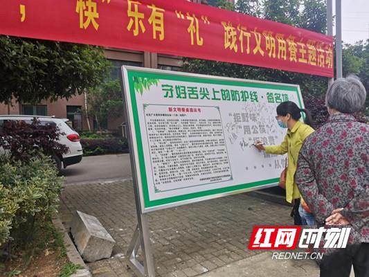 马坡岭街道安子岭社区居民在签名墙上签下自己的名字。.png