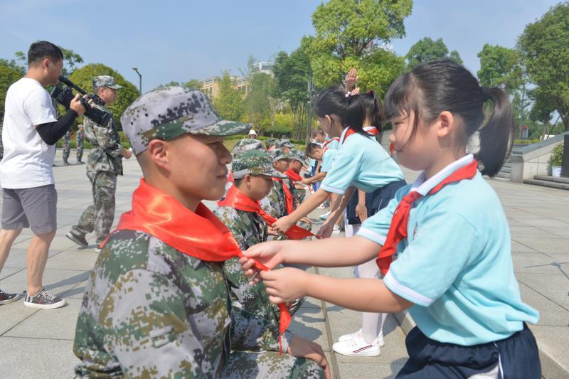小学生为新兵敬献红领巾。 王希明 朱华摄影报道