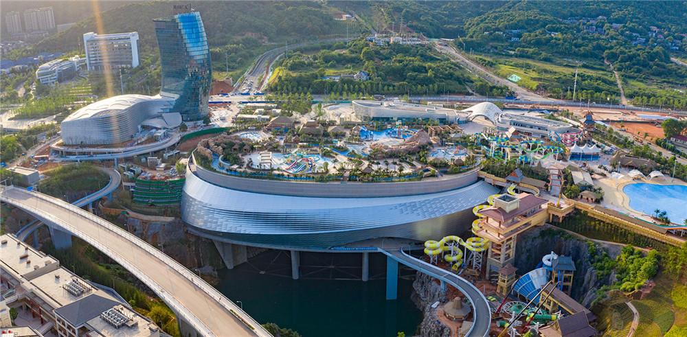 """湘江欢乐城被誉为地平线下的""""奇迹"""",这里曾经是一个因采石而留下的深达百米、面积近18万平方米的巨型矿坑,如今变身""""世界唯一悬浮于百米深坑之上娱雪嬉水为一体的主题乐园""""。"""