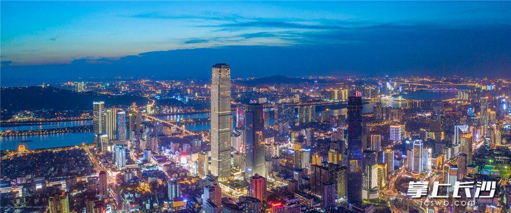 """空俯瞰镜头里的湘江东岸,高楼林立,灯光绚烂,繁华都市散发着迷人的气质。近年来,通过湘江两岸夜景亮化提质改造,长沙用五光十色的灯光点亮了""""山、水、洲、城""""特色城市名片。"""