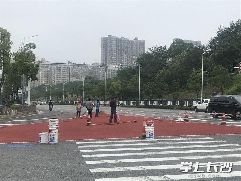 新姚路新韶路口,施工人员正在铺安全岛。