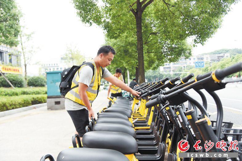近日,在长沙马王堆路上,美团电单车运营专员将停车位上的车辆摆放整齐。长沙晚报全媒体记者 刘琦 摄