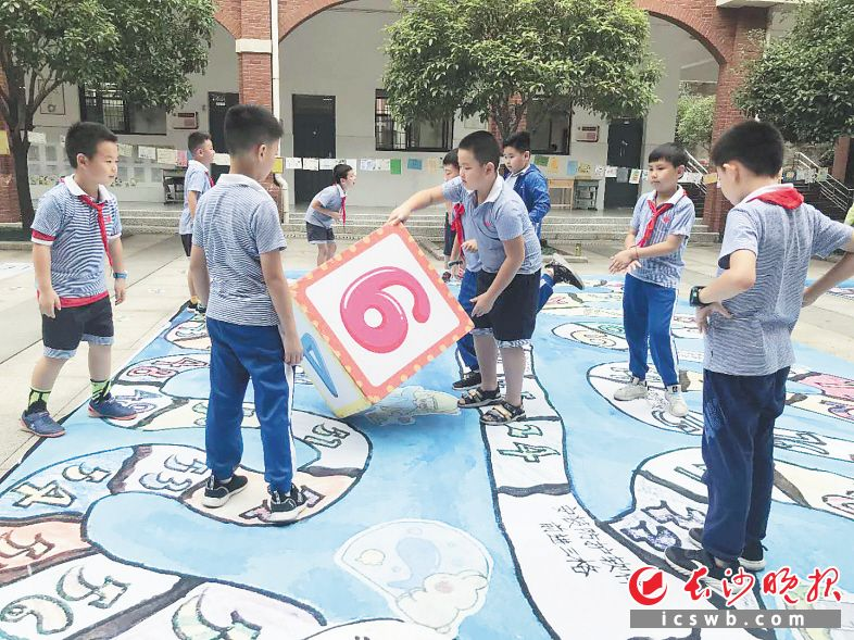 """学生掷骰子,在校园里走""""安全棋""""。  长沙晚报通讯员 王静 摄"""