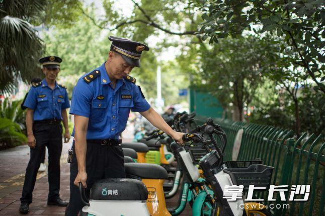 定王大厦附近,芙蓉区行政执法大队执法人员对共享单车(助力车)进行规范摆放。长沙晚报全媒体记者 黄启晴 摄