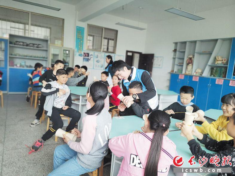 志愿者在关山学校进行了一堂科普教学,用一次性纸杯、胶带和橡皮筋制作简单的飞行器,让学生们感受到科学知识的神奇。  长沙晚报通讯员 贺芊郁 摄