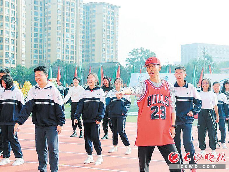 金亚骏(红衣)在校运会开幕式上和学生一起跳舞。  长沙晚报全媒体记者 刘俊 摄