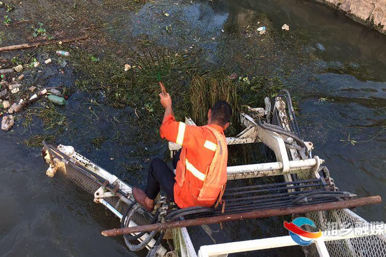 作业人员借助工具奋力打捞河面垃圾.jpg