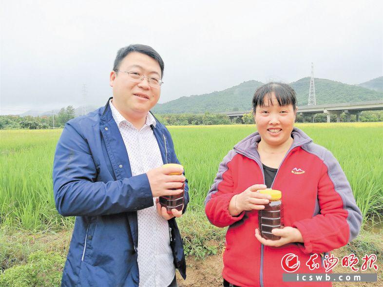 在长龙新村驻村帮扶第一书记周文超(左)的帮助下,贫困户潘群芳靠着养蜂脱贫。