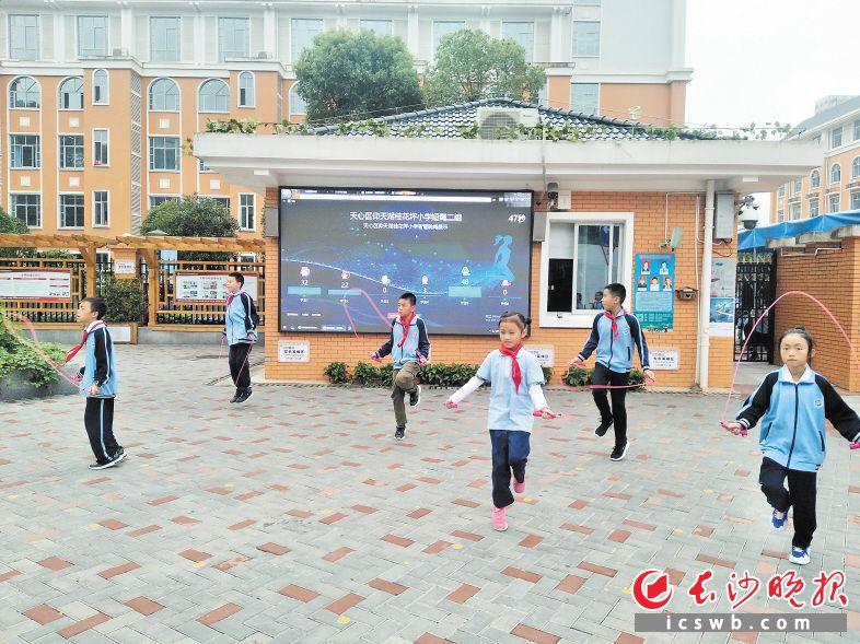 桂花坪小学校门口,几名小学生正在跳绳,大屏幕上实时显示他们的跳绳数。长沙晚报全媒体记者 陈良 摄
