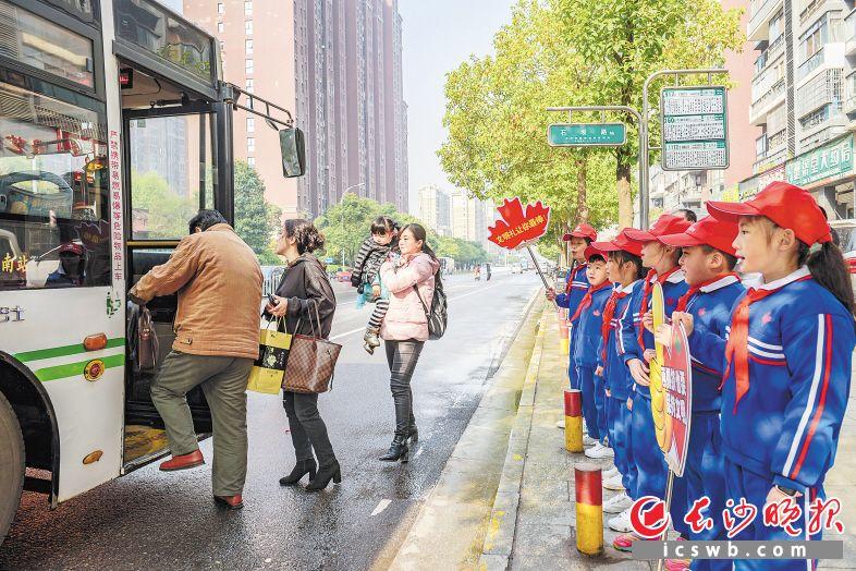 雨花区石坝路公交站台边,来自雨花区枫树山大桥小学的孩子们举着排队礼让宣传牌,向等候公交的市民宣传排队礼让。陈飞 摄