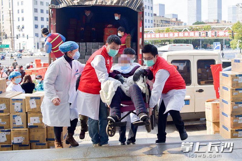 疫情期间,在长沙市公共卫生救治中心,志愿者小心翼翼地将新冠肺炎确诊患者转入隔离病区。杨蔚然 宁瑜 摄