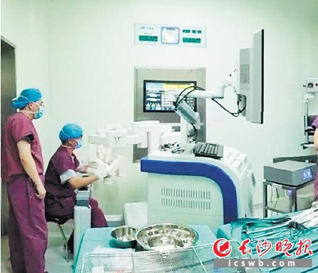 """由中南大学湘雅三医院与天津大学共同研发的新型微创新一代手术机器人""""妙手S"""",已成功运用于肝胆胰外科等。图为医生操作机器人正在手术中。医院供图"""