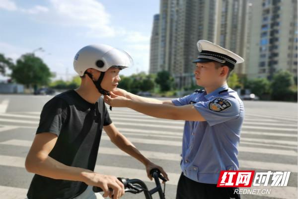 芙蓉交警大队民警民警王琼为共享电动车驾驶员佩戴头盔。_meitu_2.jpg