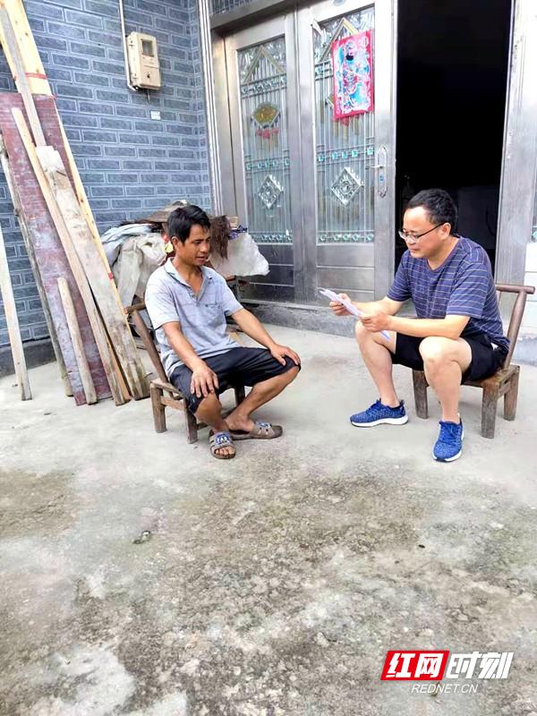 帮扶干部龙仕勇(右)向林顺清宣传党的惠民政策。.jpg