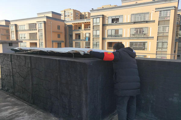 社区网格员正在对山水印象小区疑似房屋违建进行仔细查看.jpg