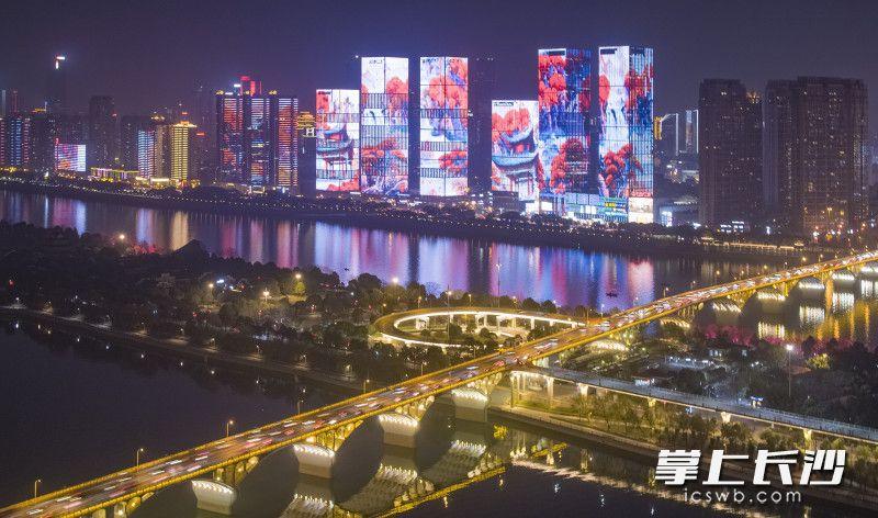 升级后的万达广场楼宇群外墙上,灯光绘出万山红遍的爱晚亭景象。