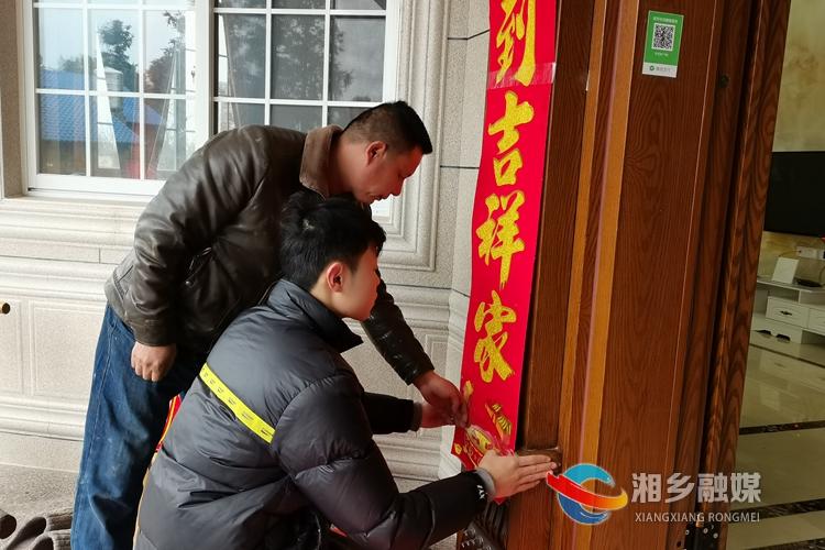 李雪锋和儿子一起贴春联。.jpg
