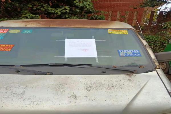 社区网格员对停放的僵尸车粘贴移车温馨提示.jpg